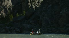 Anglers in boat pass below cliff and then Road Stock Footage