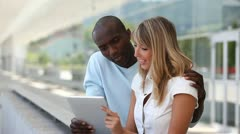 Couple using electronic tablet in town Stock Footage