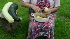 Senior woman apron peel shave clean potato knife courgette stump Stock Footage