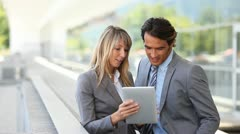 Business team using electronic tablet outside offices building Stock Footage