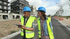 Engineers walking by buidlings under construction Stock Footage