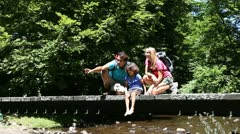 Family sitting on bridge over mountain river Stock Footage