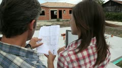 Couple checking construction plan on site Stock Footage