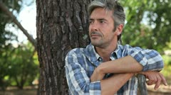 Closeup of mature man relaxing by tree Stock Footage