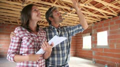 Stock Video Footage of cheerful couple standing inside house under construction