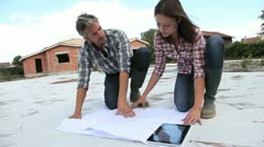 couple checking construction plan on site - stock footage