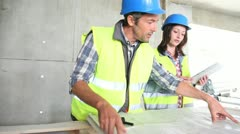 Workteam checking blueprint inside house under construction Stock Footage