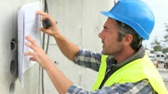 construction manager reading plan and using walkie-talkie - stock footage