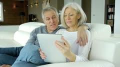Senior couple in sofa using electronic tab Stock Footage