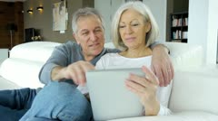 Senior couple in sofa using electronic tablet Stock Footage