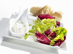A mixed leaf salad with a creamy goats' cheese dressing Stock Photos