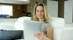 blond woman using electronic tablet at home - stock footage