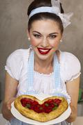 A retro-style girl holding a heart-shaped puff pastry cake Stock Photos