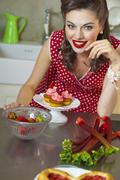 A retro-style girl with strawberry muffins, strawberries and rhubarb Stock Photos