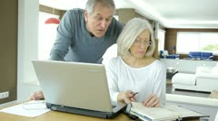 Senior couple working at home on laptop computer Stock Footage