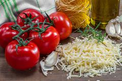 Grated cheese and tomatoes on a board Stock Photos