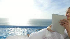 Woman using electronic tablet by swimming pool Stock Footage