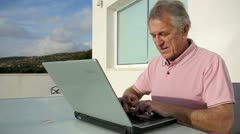 Senior man surfing on internet outside the house Stock Footage