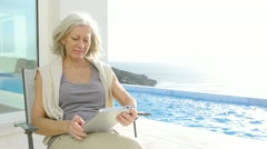 Senior woman sitting by a pool with electronic tab Stock Footage