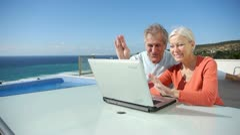 Senior couple waving into webcam Stock Footage