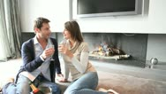 Stock Video Footage of cheerful couple drinking champaign by fireplace