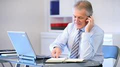 Senior businessman talking on the phone in office Stock Footage