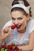A retro-style girl eating fresh strawberries Stock Photos