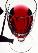 A glass of red wine and a corkscrew (transmitted light) Stock Photos