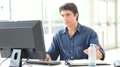 Office worker drinking water in front of desktop computer Stock Footage