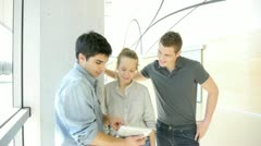 students in school hallway using electronic tablet - stock footage