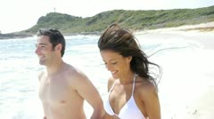 Couple in swimsuit running on the beach Stock Footage