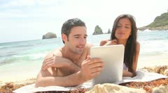 couple at the beach using electronic tablet - stock footage