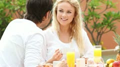 couple sitting at resort table for breakfast - stock footage