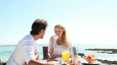 couple having breakfast by blue lagoon - stock footage