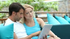 Couple sitting in sofa with electronic tablet Stock Footage