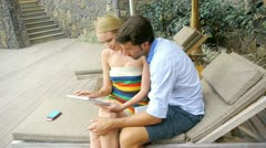 Couple on vacation using electronic tablet Stock Footage