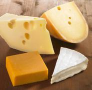 Four pieces of cheese (Emmentaler, Gouda, Cheddar and Brie) Stock Photos