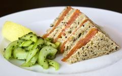 Smoked salmon sandwich and cucumber salad and lemon Stock Photos