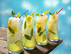 Four Mango Lime Mojitos with Straws on a Table - stock photo