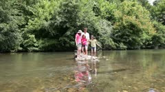Family crossing river in summer Stock Footage