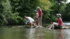 Family sitting in river in summer Stock Footage