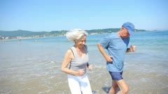 Senior couple jogging on a sandy beach Stock Footage
