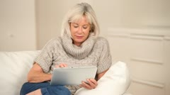 Senior woman sitting in sofa with electronic tablet Stock Footage