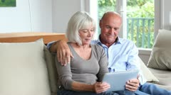Senior couple using electronic tablet at home Stock Footage