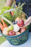 A woman showing apples from a basket of fresh fruit and vegetables - stock photo
