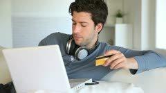 Young man buying music on internet with tablet Stock Footage