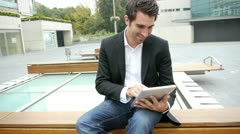 Man websurfing on electronic tablet on public bench Stock Footage