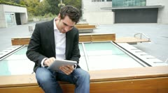 man websurfing on electronic tablet on public bench - stock footage