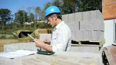construction manager using electronic tablet on building site - stock footage