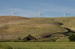 abandoned farmstead with wind turbine - stock photo